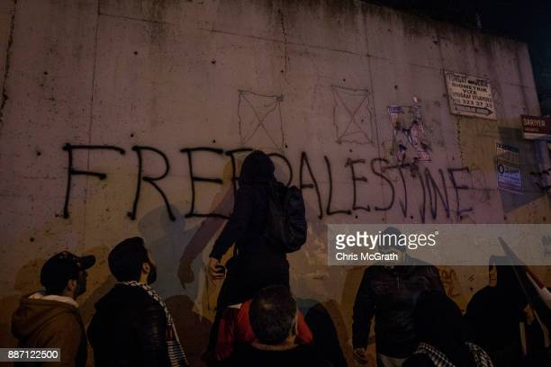 A protesters spray paints 'Free Palestine' on a wall outside the US Consulate on December 6 2017 in Istanbul Turkey People gathered to protest after...