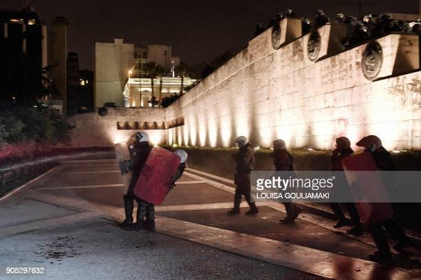 Protesters spray red pain at police in front of the Greek parliament in Athens on January 15 during a parliamentary vote on controversial reforms...