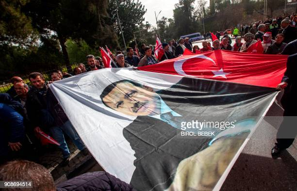 TOPSHOT Protesters spread a large banner depicting Turkish President Recep Tayyip Erdogan alongside another of a Turkish flag as they walk in a...