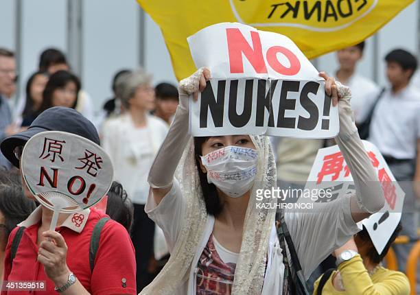 Protesters stage a demonstration march in Tokyo on June 28 2014 against reopening the Sendai nuclear power plant operated by Kyushu Electric Power...