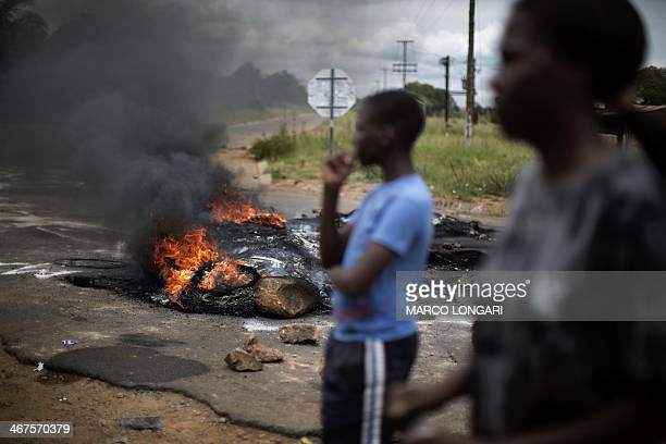 Protesters stand amid burning tires at a crossroad in Hebron near Pretoria on February 7 2014 during a protest for basic government services South...