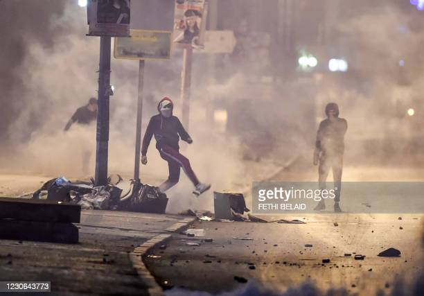 Protesters stand amidst fumes as they block a street during clashes with security forces in the Ettadhamen city suburb on the northwestwern outskirts...