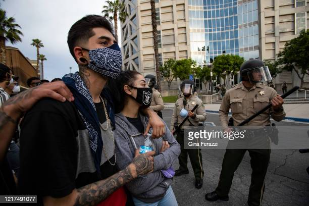 Protesters stand arminarm after marching to the Robert Presley Detention Center where they were met with a road block of law enforcement during a...