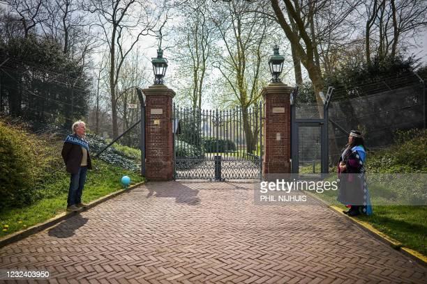 Protesters stand at the gates of the Catshuis in The Hague on April 19 2021, as part of a climate vigil started by action groups Extinction Rebellion...
