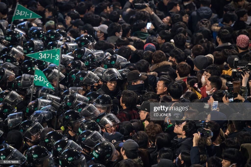 TOPSHOT - Protesters stand before police during an anti-government protest in the Gwanghwamun area of central Seoul on November 12, 2016. Up to one million people were expected to take to the streets of Seoul to demand the resignation of scandal-hit President Park Geun-Hye, in one of the largest anti-government protests in decades. / AFP PHOTO / Ed JONES