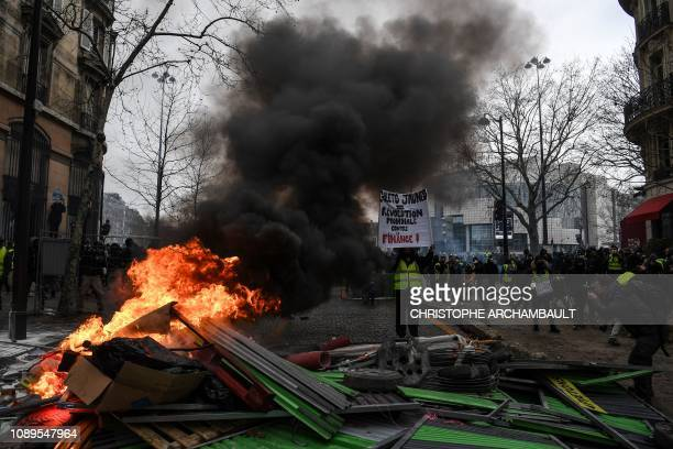 TOPSHOT Protesters stand behind a burning barricade during an antigovernment demonstration called by the yellow vests movement near the Place de la...