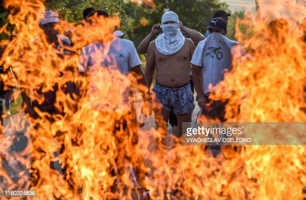 Protesters stand behind a burning barricade during clashes between supporters of Kyrgyzstan's former president and law enforcement, in the village of...