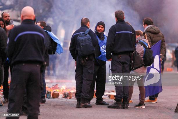 Protesters stand behind a burning barricade outside the Fresnes prison near Paris on January 15 during a demonstration by prison guards after three...