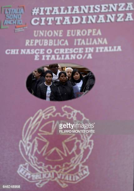 Protesters stand behind a placard representing an Italian passport during a demonstration to ask for a reform of the citizenship law in Italy, on...