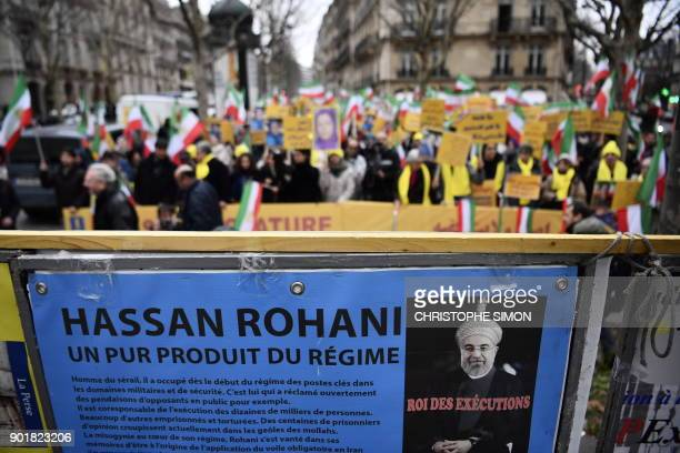 Protesters stand behind a placard with a portrait of Iranian President Hassan Rouhani during a demonstration in support of the Iranian people amid a...