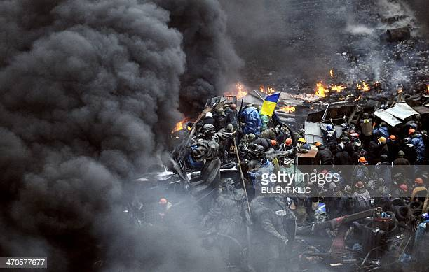 Protesters stand behind burning barricades during a faceoff against police on February 20 2014 in Kiev Hundreds of armed protesters charged police...