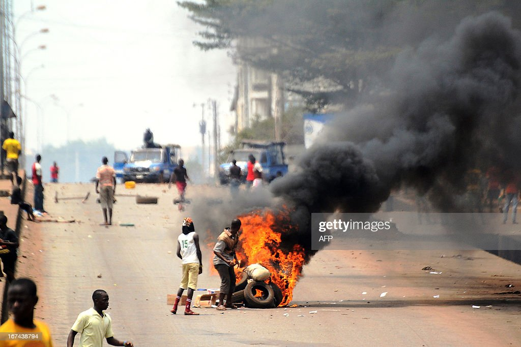 Protesters stand by burning tires during clashes with Guinea's police at the end of a demonstration on April 25, 2013 in Conakry. A week after violence erupted in the Guinean capital's streets, fresh demonstrations were called by the opposition to protest against the 'unilateral' decision of the government of President Alpha Conde to hold parliamentary elections on June 30.