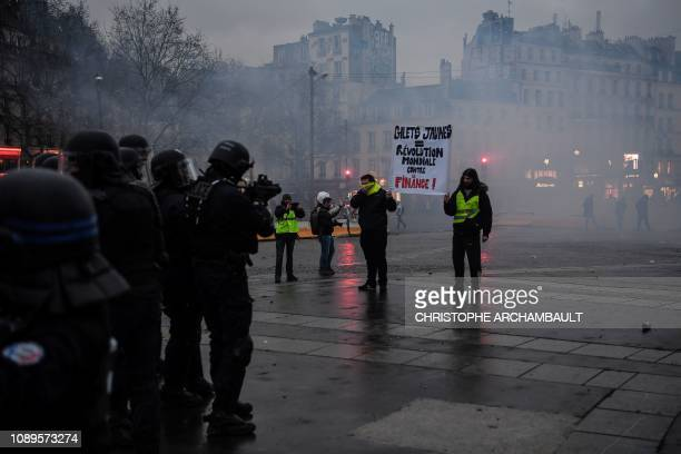 Protesters stand facing police during the dispersal of an antigovernment demonstration called by the yellow vests movement on the Place de la...
