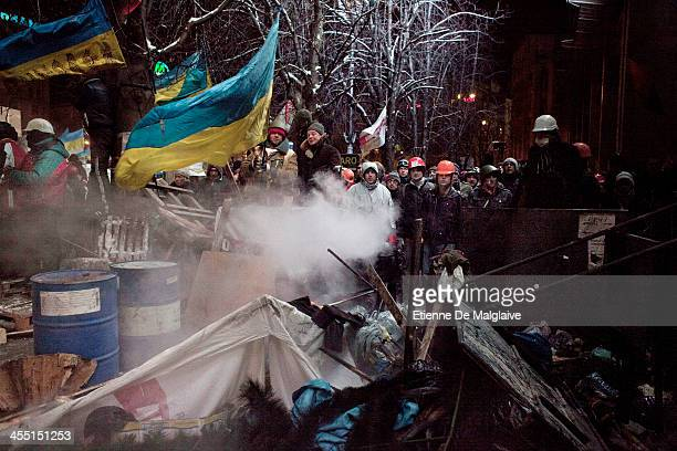 Protesters stand guard on a barricade outside the Trade Union building during a face off with riot police after authorities launched an early morning...