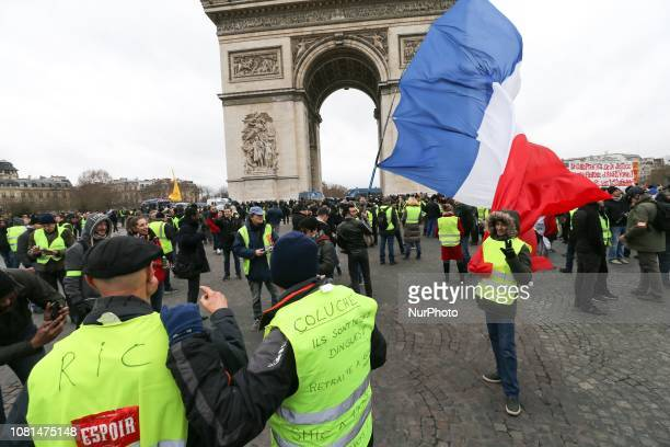 Protesters stand holding a French flag near the Arc de Triomphe on the Place de l'Etoile in Paris during an antigovernment demonstration called by...