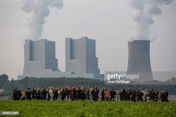 Protesters stand in an open field as German policemen surround them with the RWE Power AG power plant in the Rhineland mines region west of Cologne...
