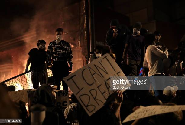 Protesters stand in front of the 3rd precinct police building as it burns during a protest on May 28, 2020 in Minneapolis, Minnesota. Today marks the...
