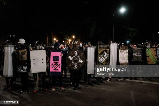 Protesters stand in preparation for conflict against federal law enforcers at the Multnomah County Justice Center on July 17 2020 in Portland Oregon...