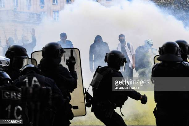 Protesters stand in tear gas smoke as they face police during clashes on the Invalides esplanade at a demonstration in Paris, on June 16 as part of a...