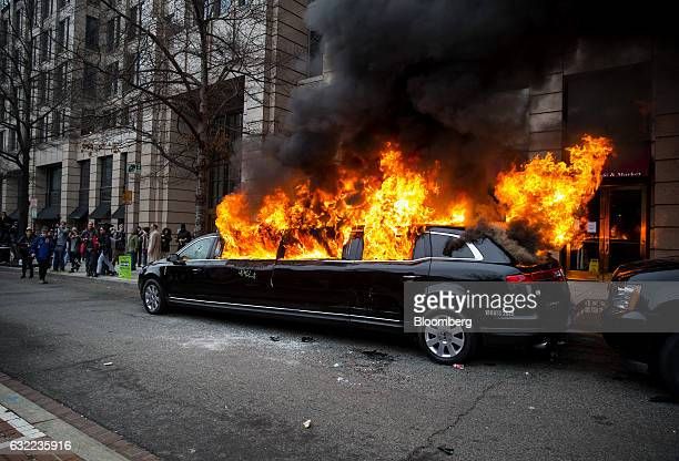 Protesters stand near a limousine on fire during a demonstration after the 58th presidential inauguration in Washington DC US on Friday Jan 20 2017...