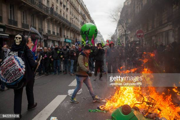 Protesters stand next a burning garbage can during a rail workers demonstration on April 3 2018 in Paris France French unions plan strikes two days...