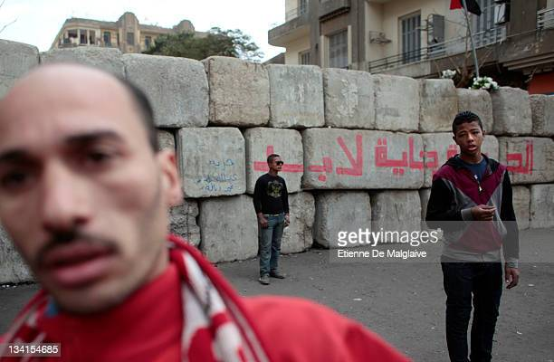 Protesters stand next to a barricade mounted by the army to keep police from clashing with protestors in Mohammed Mahmoud near Tahrir Square on...