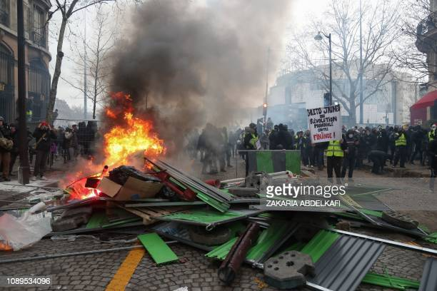 Protesters stand next to a barricade set on fire during an antigovernment demonstration called by the Yellow Vests Gilets Jaunes movement in Paris on...