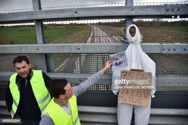 Protesters stand next to a fake hanged man on which reads '75 DB 85 times a day LGV killed me' on a bridge above a railway during a protest against...
