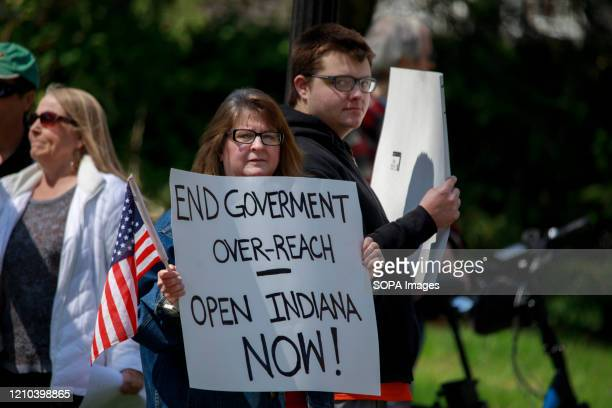 Protesters stand on the street while holding placards during the demonstration. Protesters gather outside Indiana Governor Eric Holcomb's mansion in...