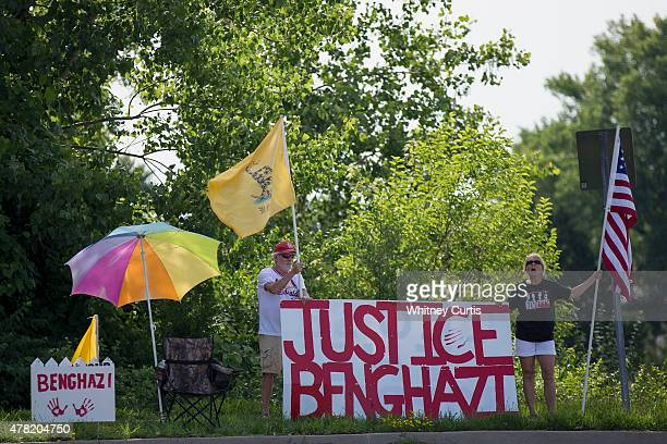 Protesters stand outside as Democratic presidential candidate and former US Secretary of State Hillary Clinton leaves after speaking to supporters on...