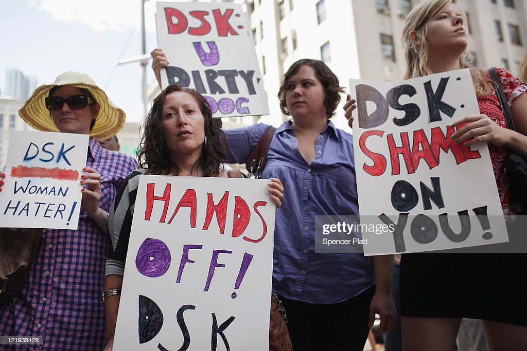 Protesters stand outside of a Manhattan court as former IMF director Dominique Strauss-Kahn exits the court on August 23, 2011 in New York City. The Manhattan District Attorney's office has filed a motion to dismiss the charges against Strauss-Kahn by Nafissatou Diallo, the hotel maid who accused Strauss-Kahn of sexual assault.