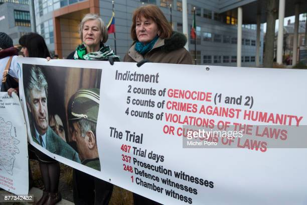 Protesters stand outside the court holding posters including one of Radovan Karadzic a Bosnian Serb former politician and convicted war criminal as...
