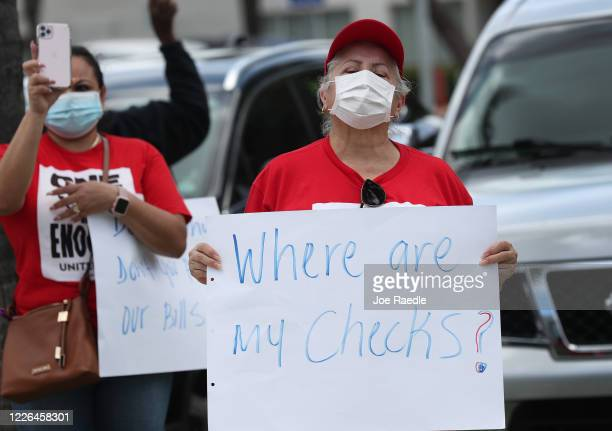 Protesters stand together asking the state of Florida to fix its unemployment system on May 22, 2020 in Miami Beach, Florida. Unemployed hospitality...