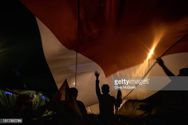 Protesters stand under a large Palestinian flag outside the Israeli Consulate during a protest against Israel on May 10, 2021 in Istanbul, Turkey....