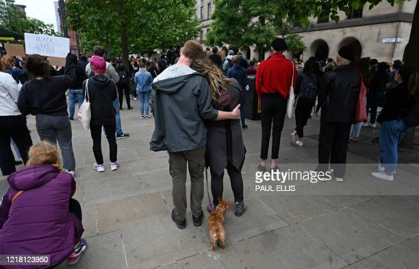 Protesters stand with a cat on a lead as they attend a demonstration in Manchester, northern England, on June 7 organised to show solidarity with the...