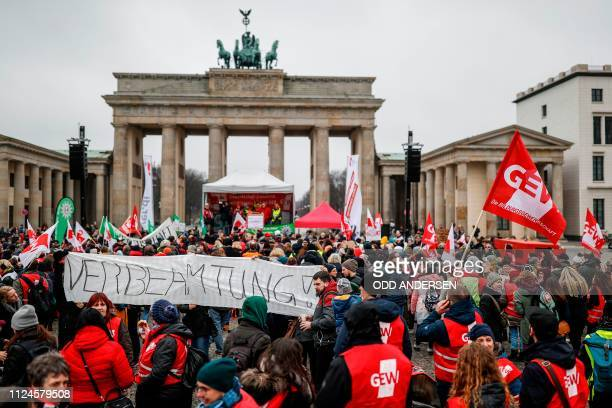 Protesters stand with flags of the GEW Education and Science Workers' Union in front of the Brandenburg Gate during a demonstration of the public...