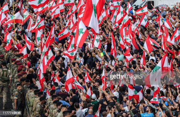 TOPSHOT Protesters stand with Lebanese national flags before Lebanese army soldiers along the side of the BeirutJounieh highway in the northern...