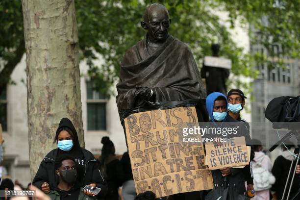 Protesters stand with placards in front of the statue of India's independence leader Mahatma Gandhi in Parliament Square central London after a...