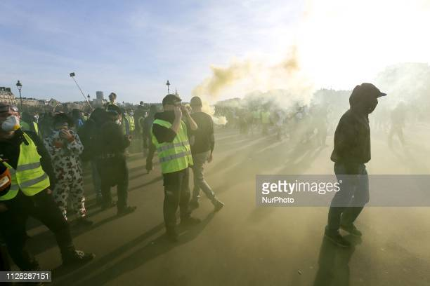 Protesters standing amid a yellow smoke during a Yellow vest antigovernment demonstration on February 16 2019 in Paris on Esplanade des Invalides...