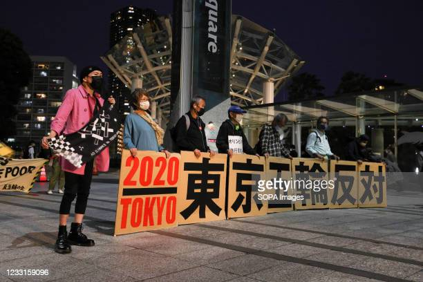 Protesters standing behind placards expressing their opinion, during the demonstration. Anti-Olympics protesters voiced their concerns regarding the...