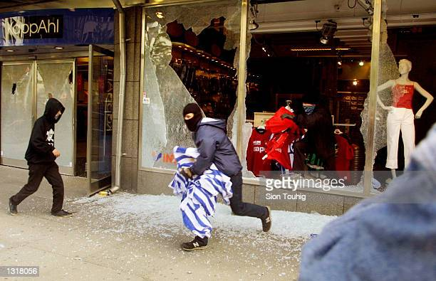 Protesters steal merchandise from a sporting goods store as fighting breaks out during a demonstration against the EU Summit June 15 2001 in...