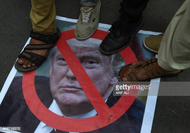 Protesters step on a picture of US President Donald Trump during a protest in Lahore on December 8 following Trump's decision to officially recognise...