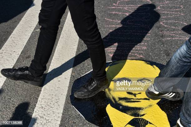 Protesters step on a sticker with an image of Russian President Vladimir Putin during a rally against the government's proposed reform hiking the...