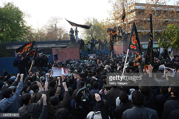 Protesters storm a security gate as they break in to the British Embassy during an anti-British demonstration in the Iranian capital on November 29,...
