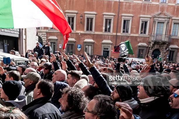 Protesters street vendors and taxi drivers make the fascist salute in front of the Democratic Party headquarters to protest against the EU directive...