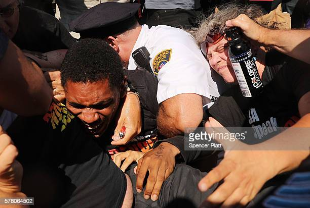 Protesters struggle with police after trying to burn an American Flag near the site of the Republican National Convention in downtown Cleveland on...