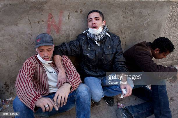 Protesters suffer from the effects of tear gas inhalation during clashes between protesters and riot police near the interior ministry February 3...