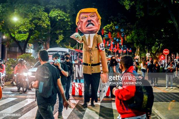 Protesters surround a dummy depicting United States President Donald Trump making a Nazi salute before burning it in Medellin, Colombia, on November...