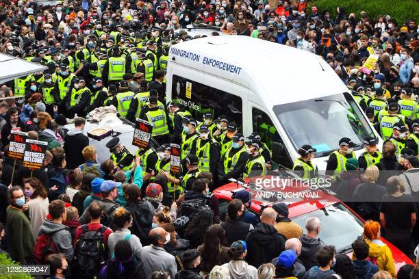 Protesters surround an Immigration Enforcement van to stop it from departing after individuals were detained in Glasgow on May 13, 2021.