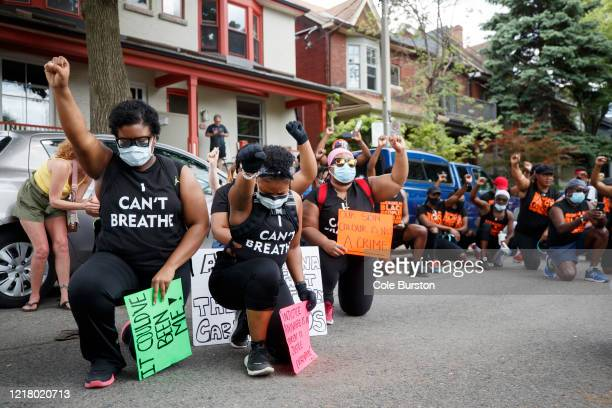 Protesters take a knee and raise their firsts during an antiracism march on June 6 2020 in Toronto Canada This is the 12th day of protests since...
